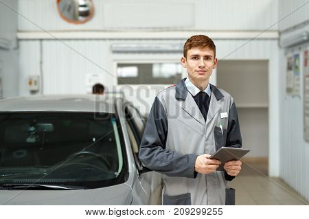 Portrait of a car mechanic in a car workshop with a tablet computer