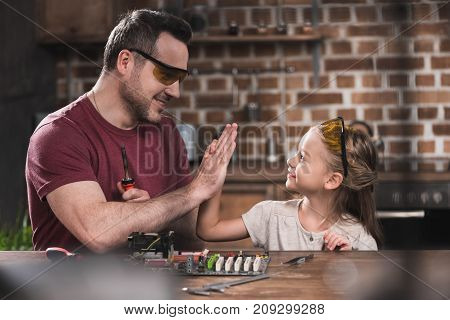 Father Giving High Five To Daughter