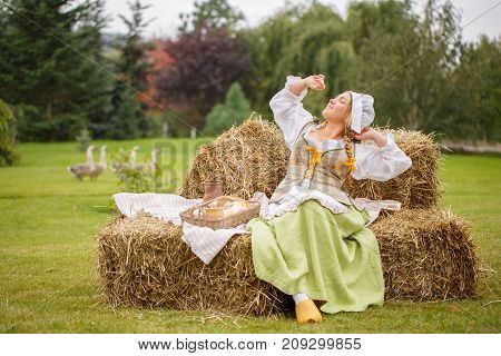 the peasant woman sips on the hay. picnic