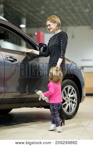 woman with daughter choose car in auto shop