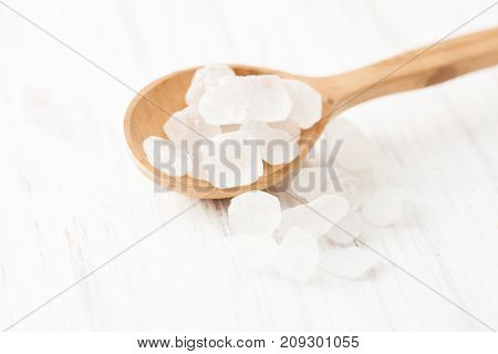 Lump Sugar In Wooden Spoon On White Wooden Table