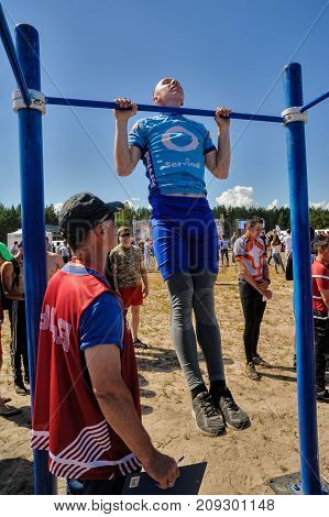 Tyumen, Russia - July 5, 2017: Race of Heroes project on the ground of the highest military and engineering school. Hitting qualifying standards of GTO. Strong man doing pull ups