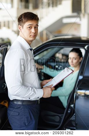 salesman presenting new car to clients dealership