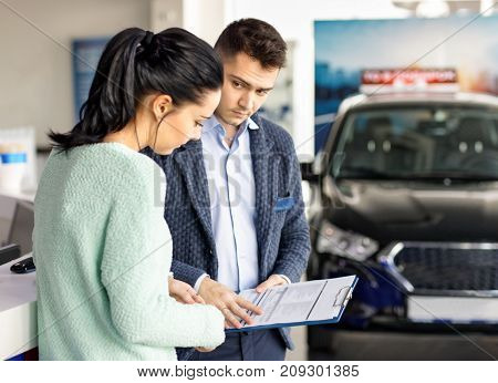 salesman presenting new car to clients auto shop