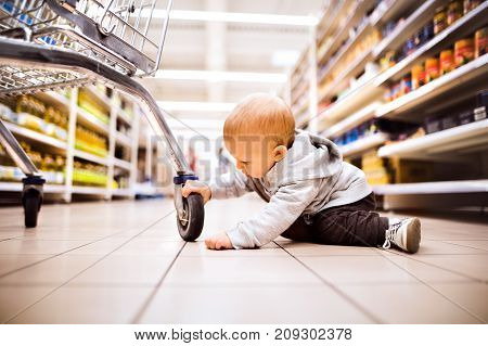 Cute little baby at the supermarket. Baby on the floor, next to shopping trolley.