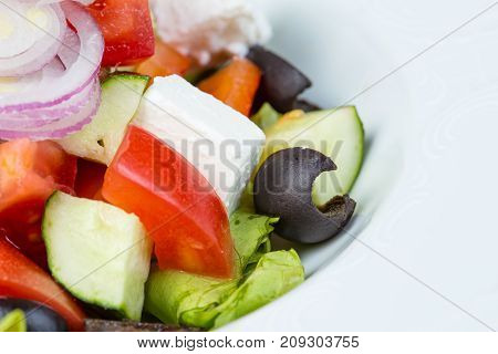 Greek vegetarian salad with red onion on white background