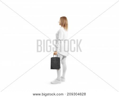 Women holding blank black craft paper bag design mock up in hand. Woman hold kraft textured purchase pack mock up. Clear shop bagful branding template. Shopping carry package in persons arm.