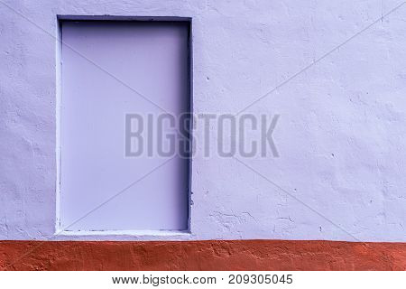 The homogeneous background of wall is dyed with a brown and purple paint. Hidden window. The background of the concrete fence.