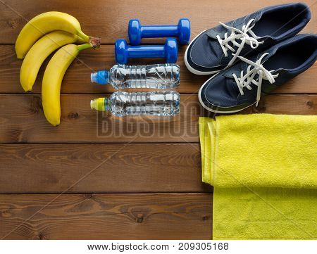 Fitness concept with sneakers dumbbells towel bottle of water and bananas on wooden table background