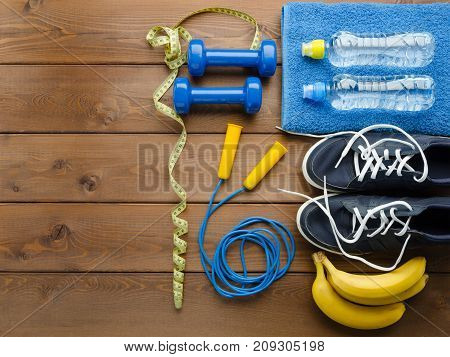 Fitness concept with sneakers dumbbells skipping rope measure tape towel bottle of water and bananas on wooden table background