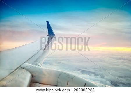 Airplane wing flying above clouds on the sunset. Selective focus. Space for text.