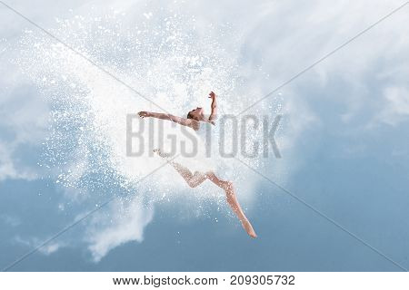 Beautiful ballet dancer jumping inside cloud of powder in front of blue sky