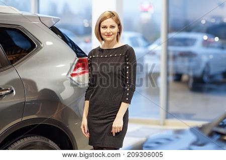 Woman smiles in the background of dealership