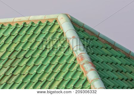 Green colored curved clay roof tiles with ridge corner. Vibrant coloured building roof.