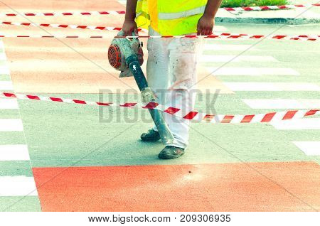 Paint job. Worker cleaning road of dirt and dust with blowing machine to prepare asphalt for painting new bicycle lane with red paint