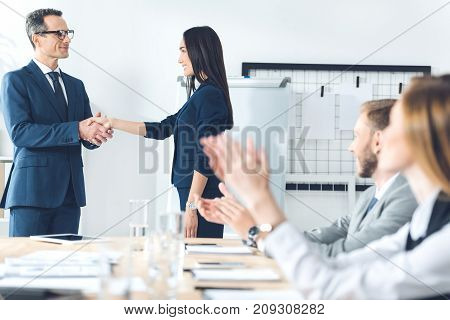 boss shaking hand of manageress at conference hall while colleagues clapping
