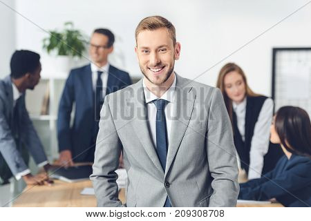 handsome young manager looking at camera with blurred businesspeople in conference hall