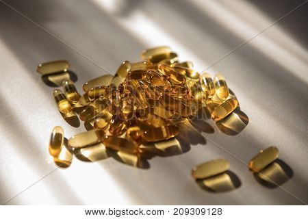 Vitamins pills of yellow color isolated on white background. Cod liver oil. Fish oil capsule pills closeup background
