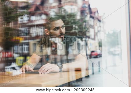A man sitting in a cafe looking through the window. The city reflects in glass.