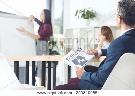 businessman with holding newspaper listening to presentation in conference hall