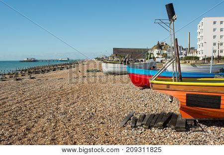 Fishing boats drawn up on shingle beach at the seafront in Worthing West Sussex England