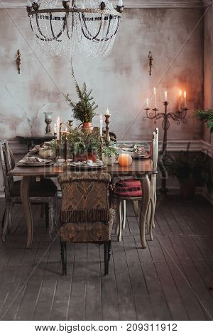 Christmas table setting. Vintage chairs, natural pine tree branches, candles. Rural or rustic style decorations. with clear concrete wall for copy text