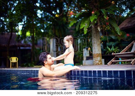 Father And Son Enjoy Relaxing In The Pool At Quiet Getaway