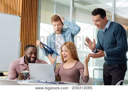 Be successful. Emotional office workers celebrating their win in competition, actively gesticulating while looking at computer