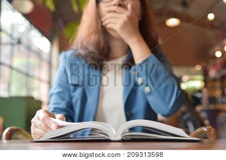 Sleepy Asian Woman in Blue shirt yawning while reading book on wooden table at coffee shop.