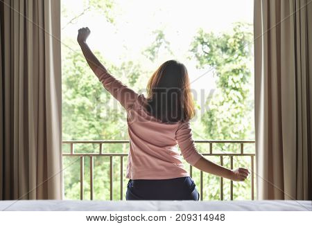 Rear view. Happy Relaxed Asian woman waking up and Outstretched her arms on green natural background at her bedroom in the morning. Resting on Holiday.