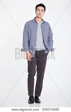 Studio portrait of a handsome young man posing confidently against a gray background