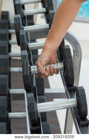 close up hand of sport man is holding dumbbell exercising working out at the gym or fitness. sports trainnings