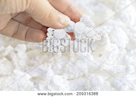 Button knot chinese : A lot of traditional chinese white knot buttons on the white background.
