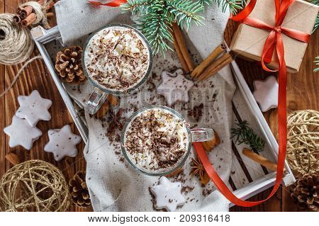 Christmas background with two latte cookies star fir branches cones gift and spices. Couple coffee with milk and homemade tasty cookies in tray on wooden background. Flat lay top view.