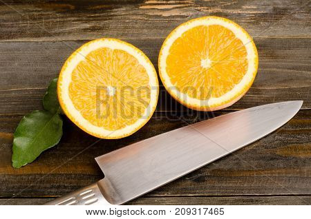 Sliced Navel orange fruit and knife on wooden background, top view