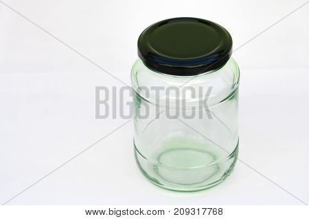 Close up glass bottle transparent blank isolated on white background with black lid.
