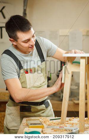 Carpenter polish round chair in workshop. Woodworker in apron work with wooden furniture, craftsman at work, professional handyman