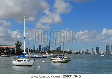 Sailboats moored on the florida intra-coastal waterway off Miami Beach with the Miami tall building skyline in the distance.