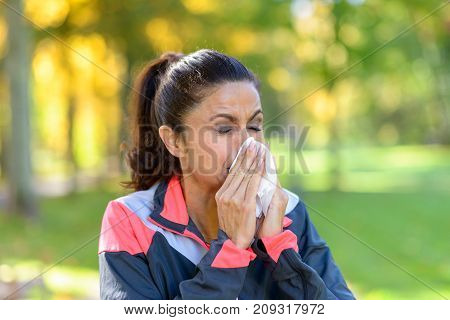 Woman Blowing Her Nose On A Tissue Outdoors