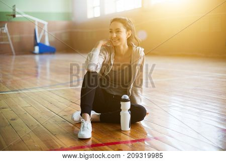 Relaxing After Training. View Of Beautiful Young Woman Sitting On The Wooden Floor