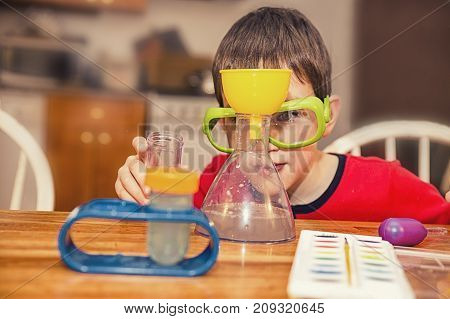boy making chemical experiments at home. child observes the chemical reaction in the flask