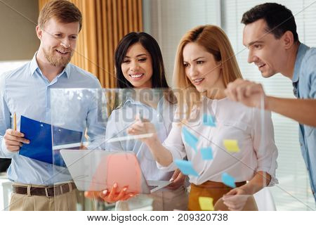 Do it quickly. Charming brunette keeping smile on her face and her blonde partner drawing graph while standing behind her colleagues