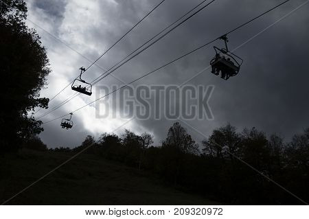 silhouettes of people in a ski lift on a mountain. funicular on the background of the stormy sky