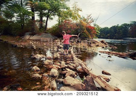 boy walks the rocks in the water to the side. the boy tries to keep his balance when walking on the slippery stones in the lake