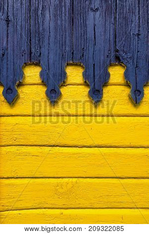 The wooden wall of the boards is painted yellow with decorative carved elements