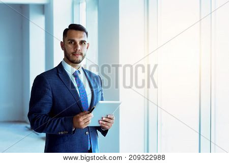 Businessman or real estate agent stands near big window in new apartment with tablet computer