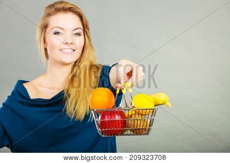 Woman Holding Shopping Basket With Fruits Inside