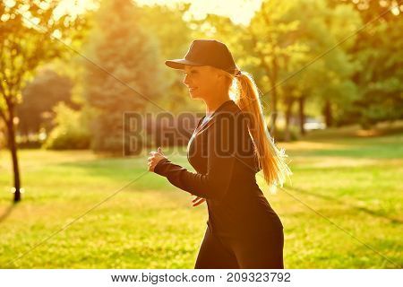 A beautiful young blonde woman wearing black clothes and baseball cap  while running in a park in the sunset