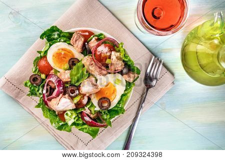 A photo of a plate of salad with canned tuna, boiled eggs, green lettuce leaves, onions, black olives, and cherry tomatoes, on a teal texture with a fork, a glass of wine, olive oil, and copy space