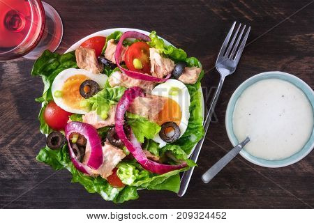 Overhead photo of a plate of salad with canned tuna, boiled eggs, green lettuce leaves, onions, black olives, and cherry tomatoes, on a dark rustic texture with a glass of rose wine and a white sauce
